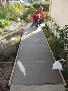 Here Steve finishes off the new concrete walkway. The board frames are now gone, and it looks good. We will keep it cordoned off for a while.