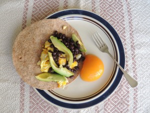 Scrambled eggs with avocado and black beans on a whole wheat flour and corn tortilla. Yum!
