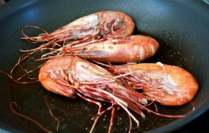 Spot Prawns cooking in a skillet with olive oil and rock salt.