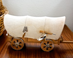 A little covered wagon, handmade in Mexico--this inexpensive E-bay find came with a tiny shovel, rifle, powder horn, barrel, and plow--everything a pioneer family might need.