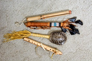 From top to bottom, a clapper stick, a deer hoof rattle, a turtle rattle, and a flute.